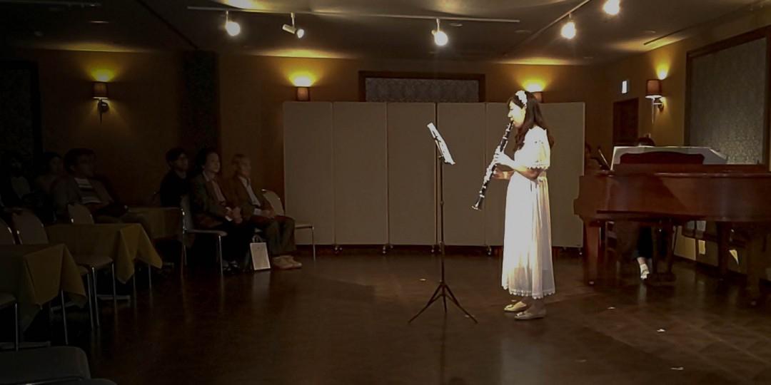 発表会のステージでライトを浴びて演奏するクラリネット奏者