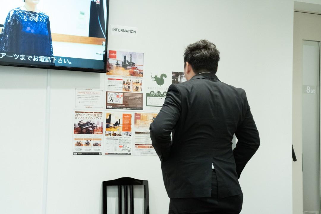 実技模試開始前に壁に貼られた教室のポスターを見る参加者