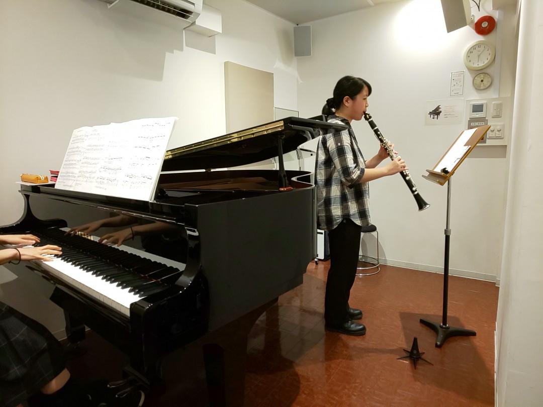 レッスンでピアニストと演奏する生徒