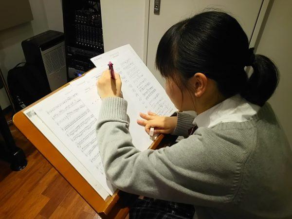 譜面台に置かれた楽譜に書き込みする生徒