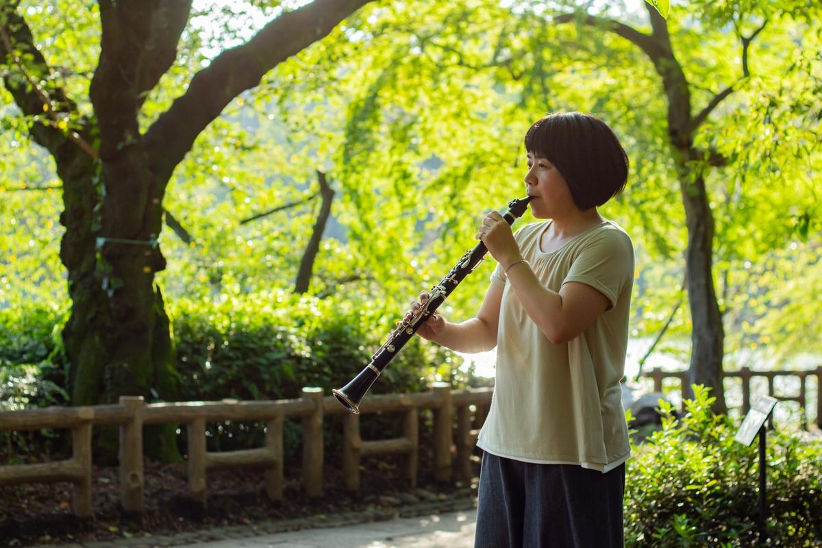 緑がきれいな公園で演奏するクラリネット奏者